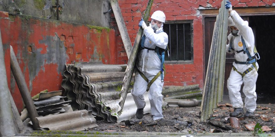 workers in hazmat suits removing asbestos from a building