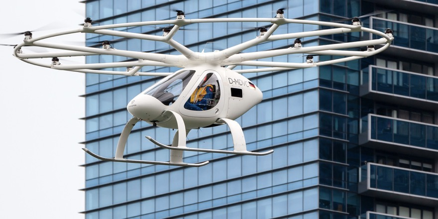 electric airplanes include this electric helicopter, the Volocopter, flying in front of a high rise tower