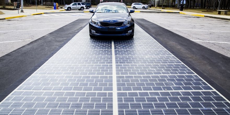 a car on a road paved with solar cells