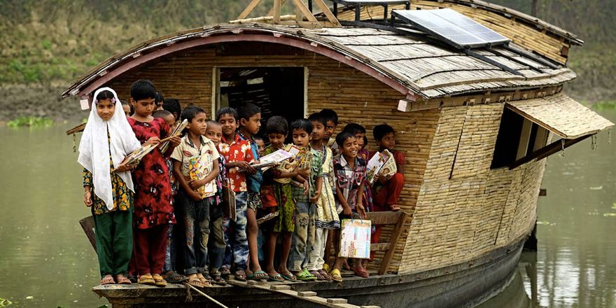 a group of smiling children on a small houseboat