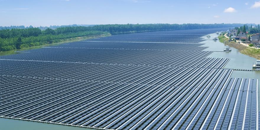 aerial photo of thousands of floating solar panels covering an entire river for miles into the distance