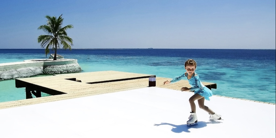 a little girl figure skating on a plastic ice rink with palm trees and ocean in the background