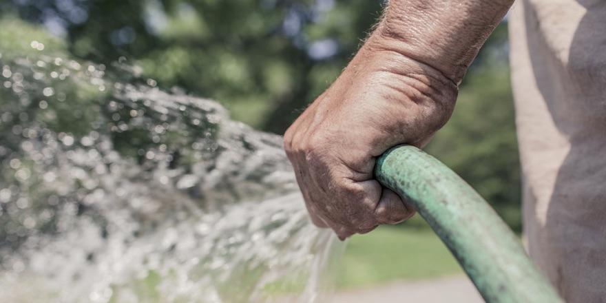 a mans hand spraying a hose