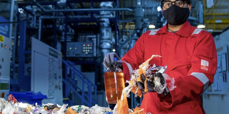 man feeding plastic into Plaxx machine